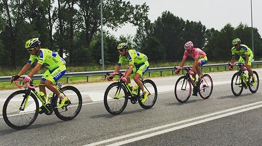 four men riding bicycles at road during daytime