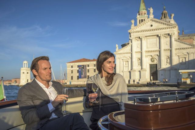 man and woman sitting on boat deck while holding wine glasses at daytime