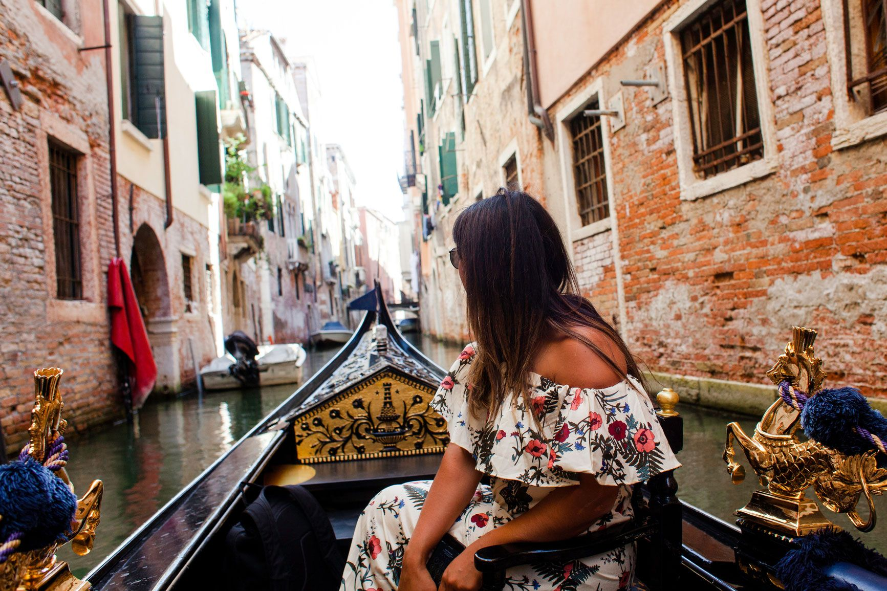 woman wearing pink floral dress sitting on boat at Venice Canal