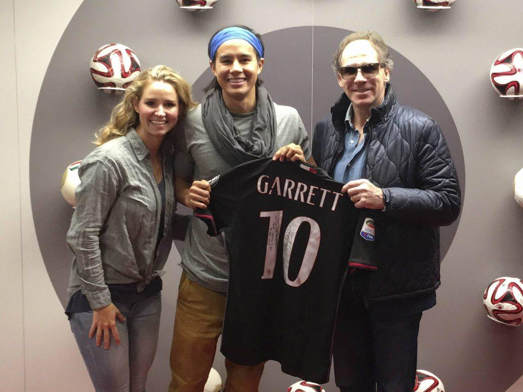 two men holding black and white Garrett 10 jersey beside woman