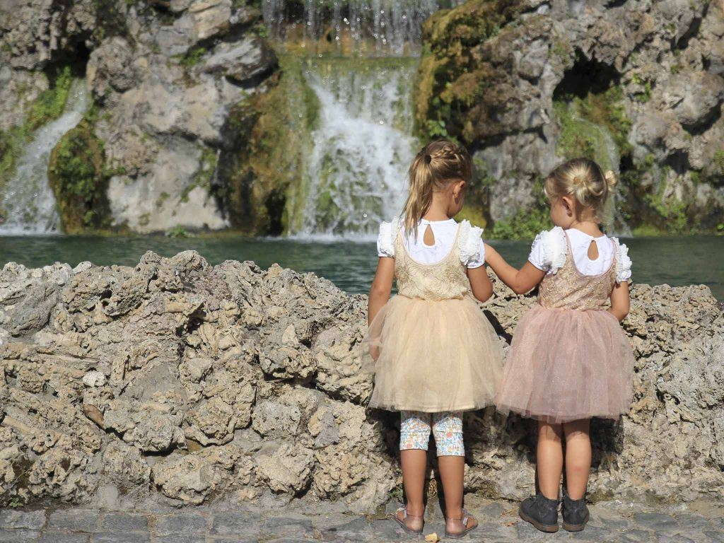 two girls standing near on the rock facing the water falls