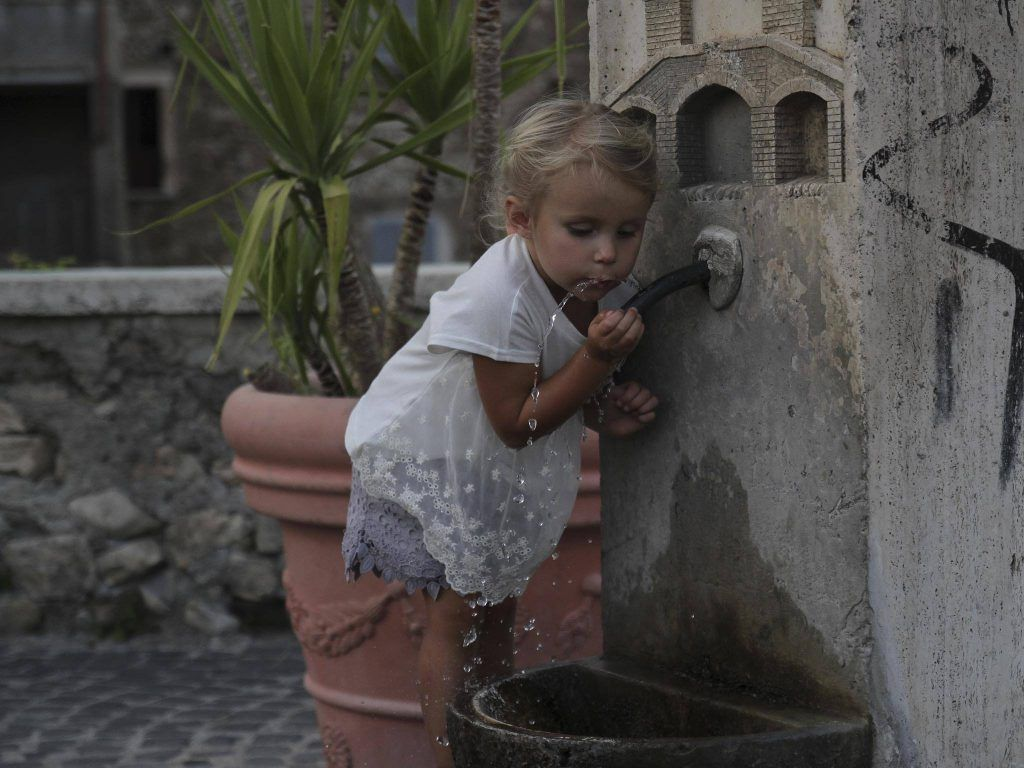 girl drinking water on faucet