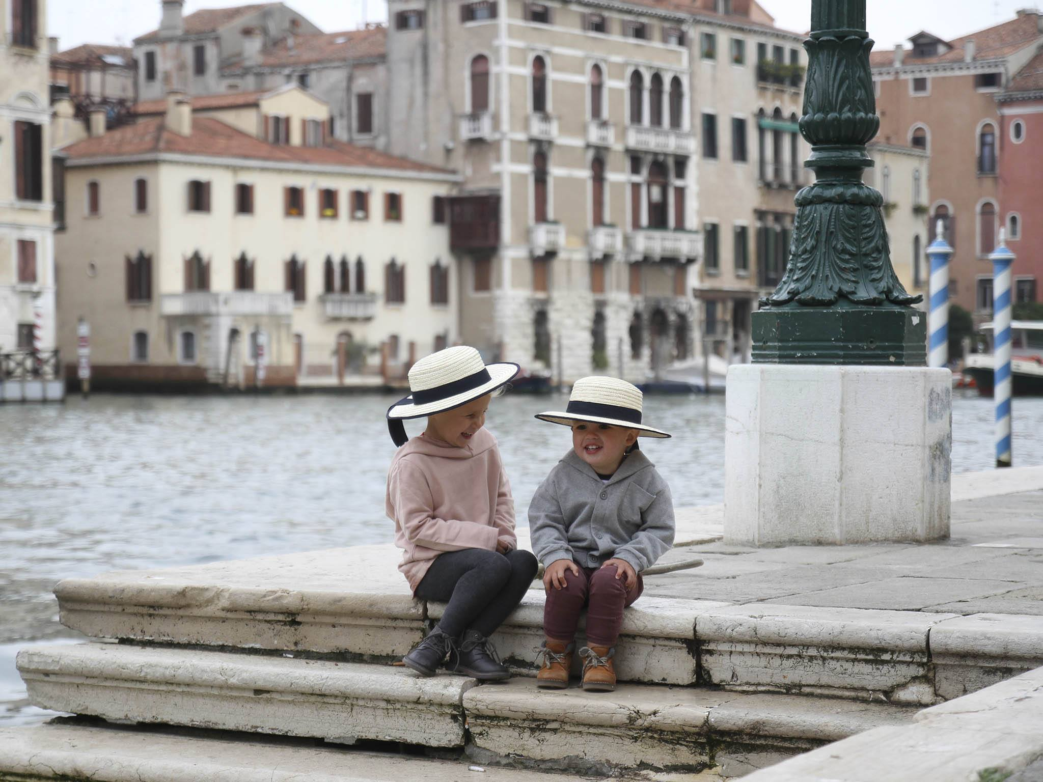 two girl and boy sitting on stairs near body of water