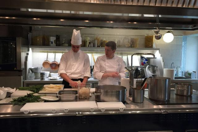 two chefs standing behind kitchen counter