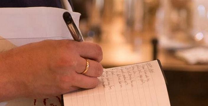 selective focus photography of person writing on black lined notebook