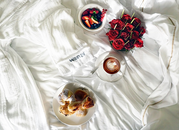 bouquet of red roses, coffee, strawberry, and breads on white textile