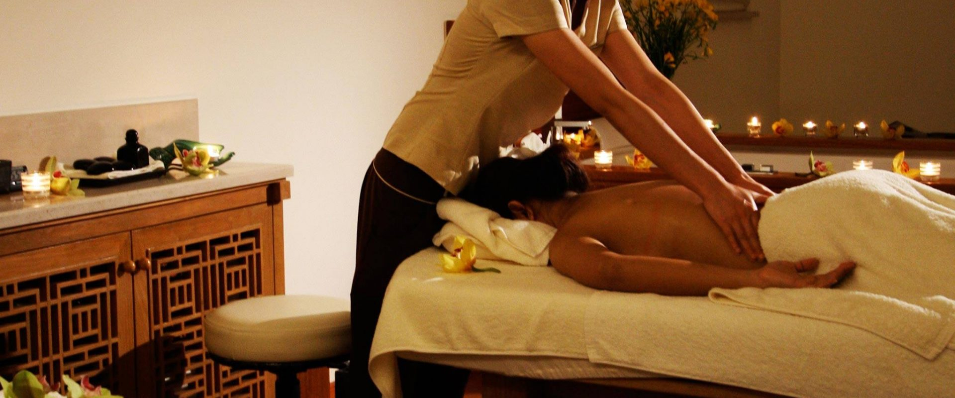 woman lying on bed while woman massaging her