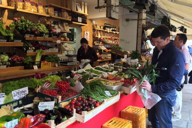 man holding vegetable near store