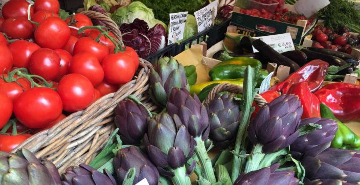 artichoke near tomatoes surrounded by assorted vegetables