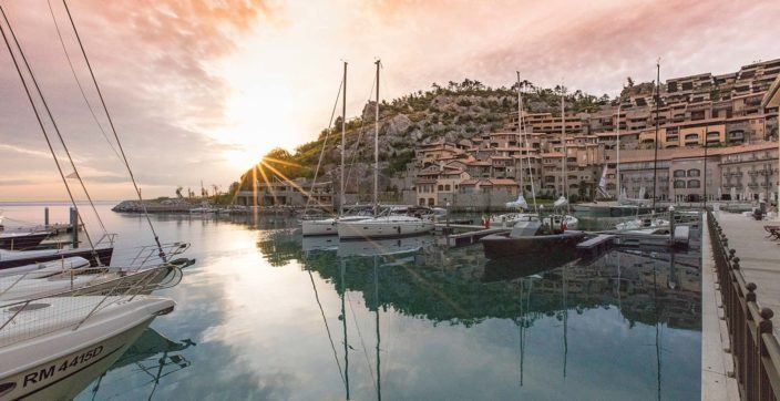 The sun setting behind a rocky hill in Portopiccolo, Italy with sailboats and crystal clear water in the foreground.