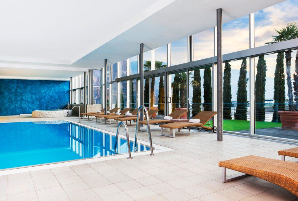 indoor swimming pool surrounded with sunlounge chairs
