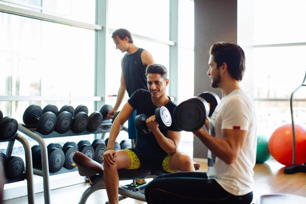 two men holding dumbbells while sitting