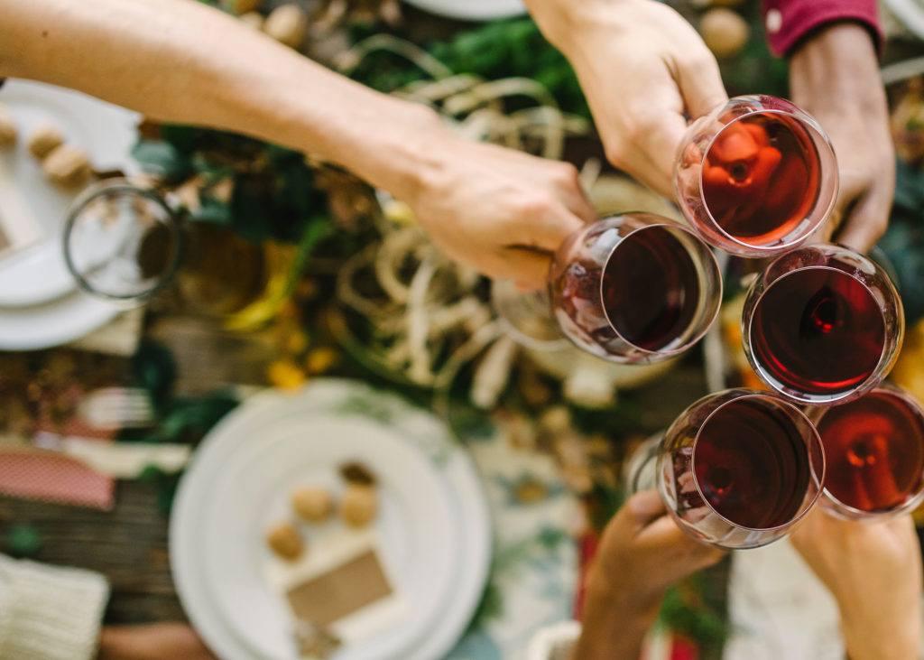 five person toasting wine glasses