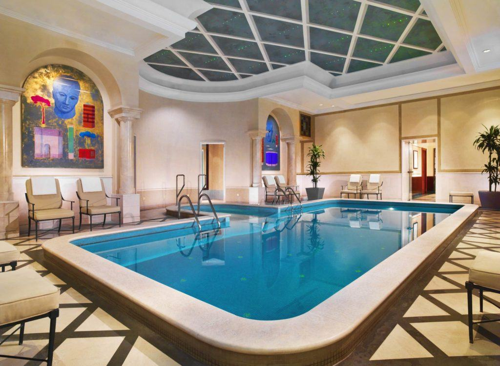 pool inside house with armchairs