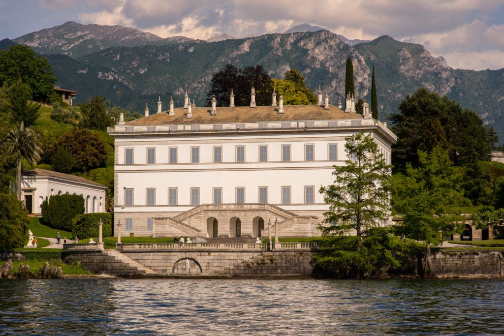 white and brown building in distance of mountain and body of water