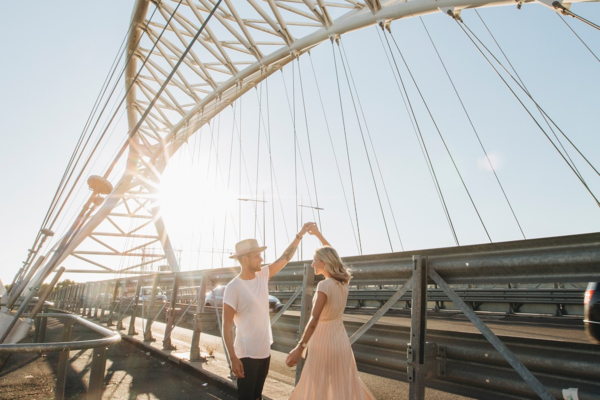 man and woman dancing beside bridge