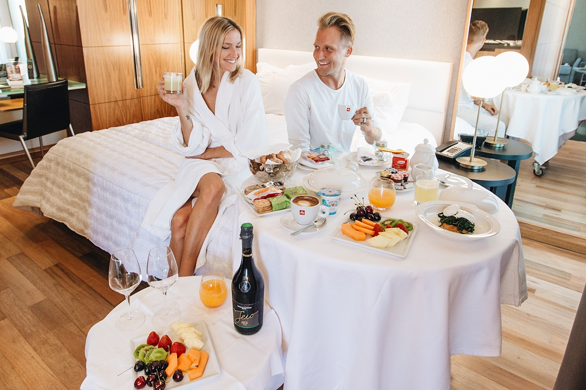 couple sitting on bed in front of table with variety of food