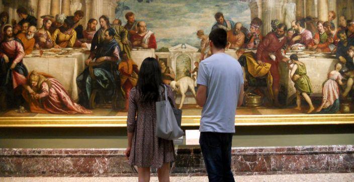 man and woman staring at painting