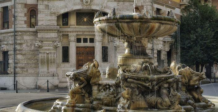 beige concrete fountain near high rise building