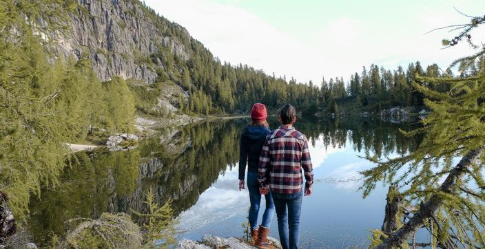 two people standing near lake