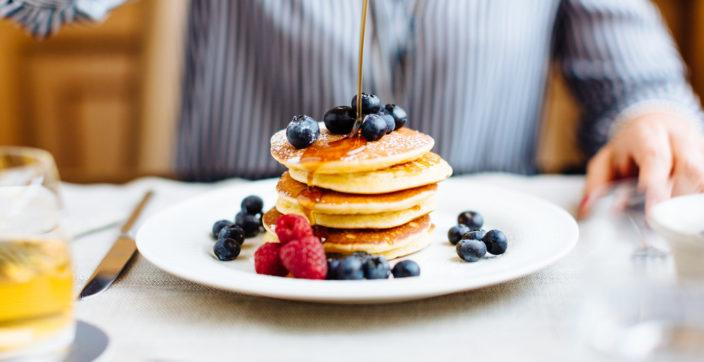 person pouring syrup on pancake with olive fruits on plate