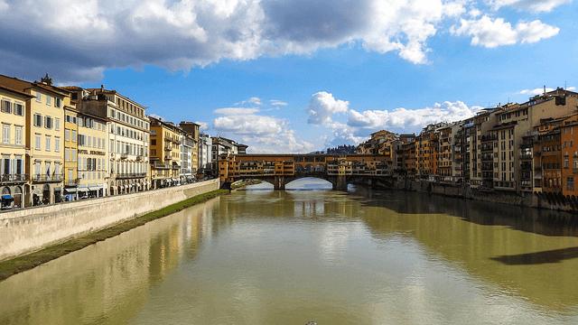 bridge above water between buildings at daytime