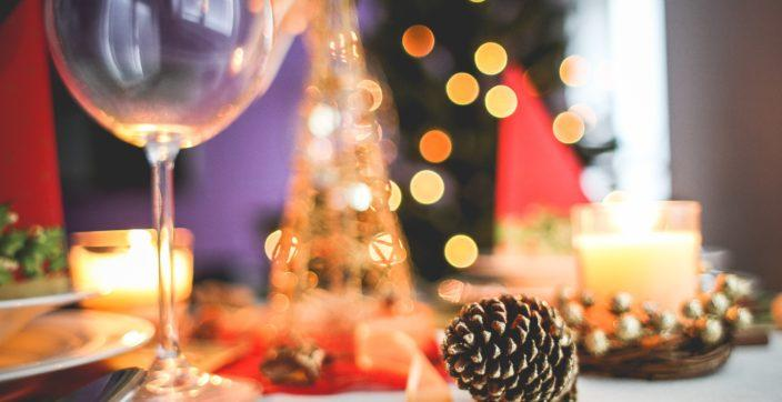 a table set decoratively with Christmas ornaments and a wine glass