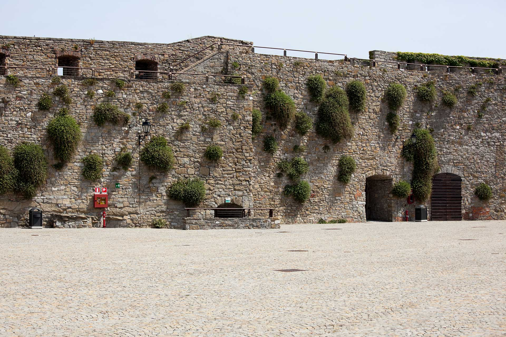 an old stone wall with green shrubs growing out of it rising up from a cobblestone courtyard