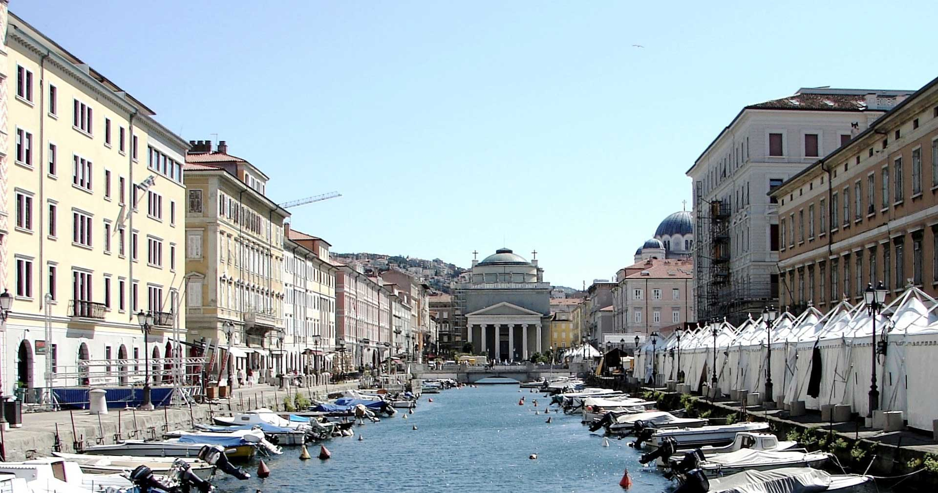 an Italian canal in Trieste lined with boats with a grand religious building at the end of it