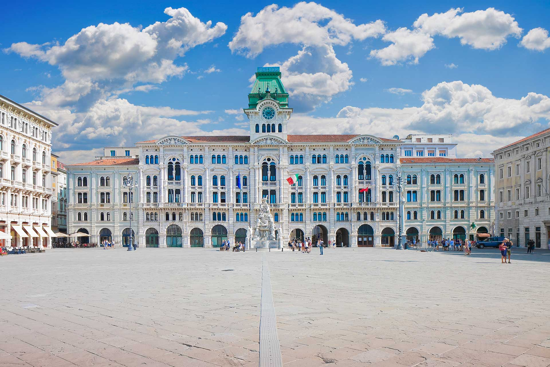a large open Italian city square on a sunny day in Trieste surrounded by beautiful nineteenth century buildings