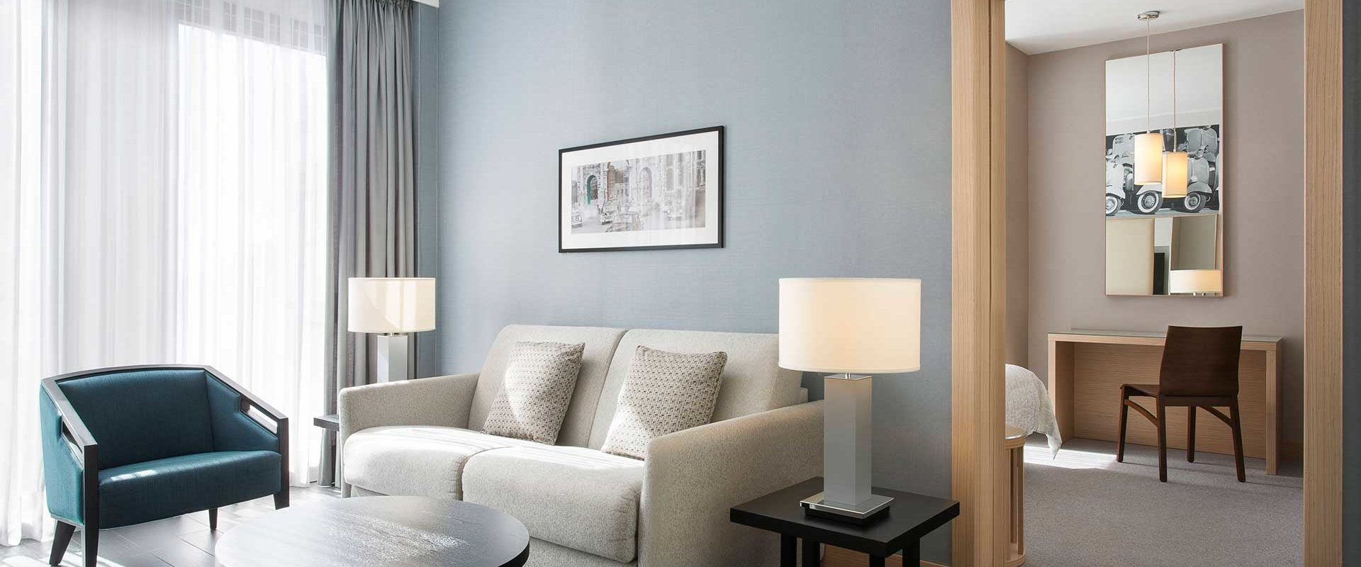 A white love-seat in a hotel suite living area with lots of natural light