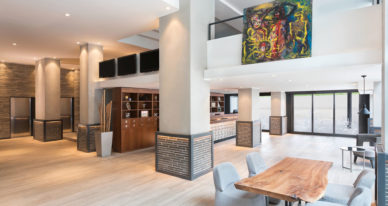 a bright, spacious, modern hotel lobby width a colorful abstract painting hanging above a seating area