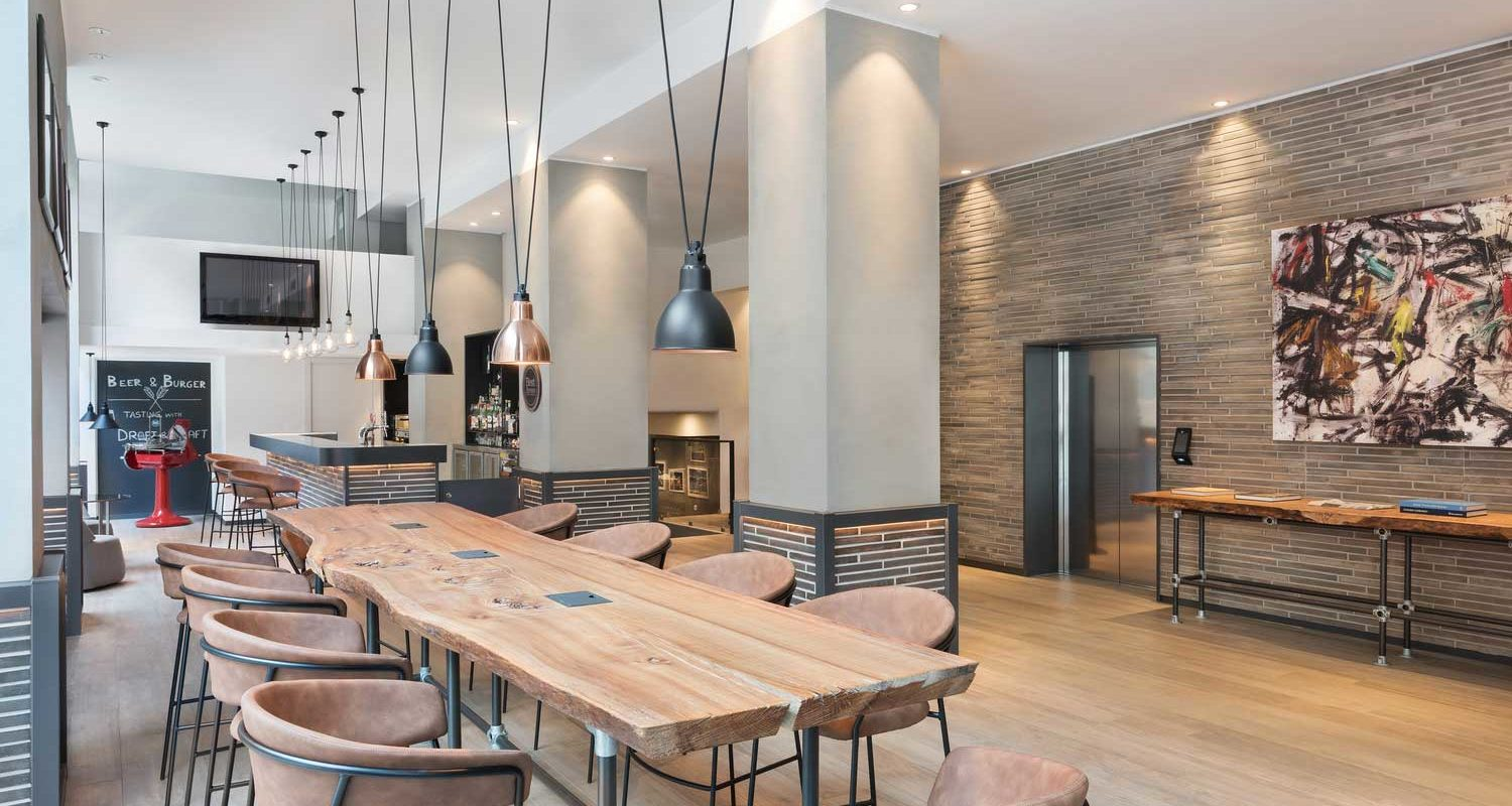 A bright, spacious, modern Italian bar with a long wood plank table surrounded by comfortable chairs.