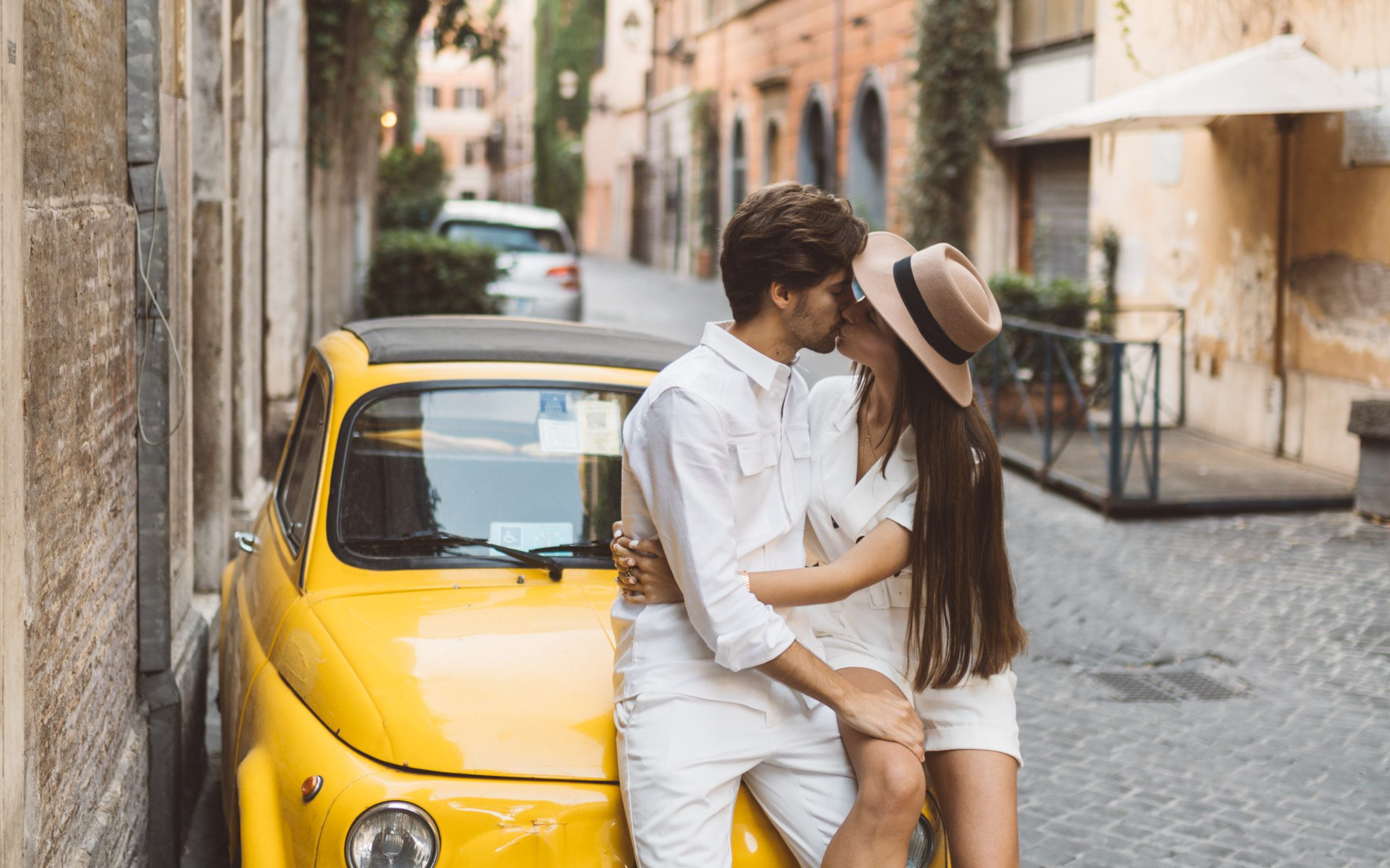 Couple kissing while sitting on a Fiat in Via Margutta in Rome