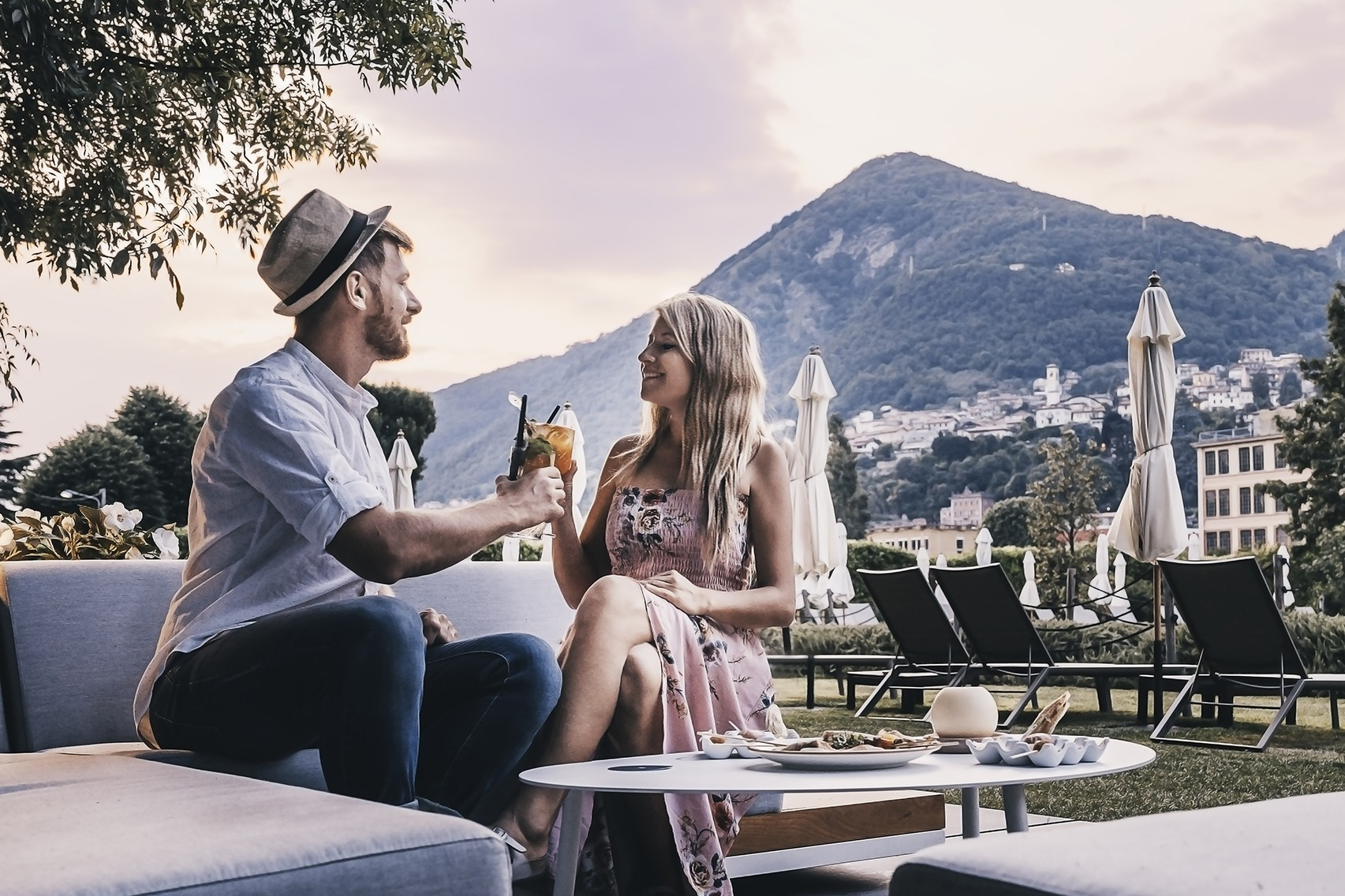 Couple having a toast in a park surrounded by mountains and trees