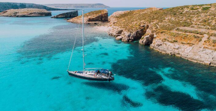 Aerial of Yacht in a crystal clear Blue Lagoon, off Comino