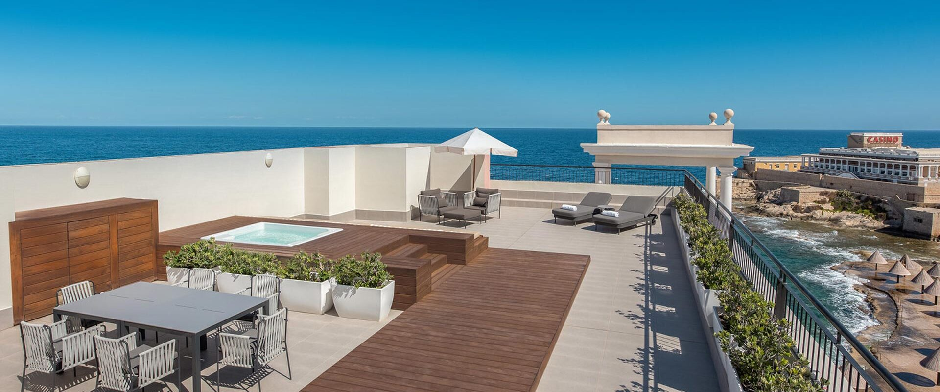large private terrace outside of a luxury ocean-side suite with a wooden walk-way to a hot tub and an outdoor table and chairs set