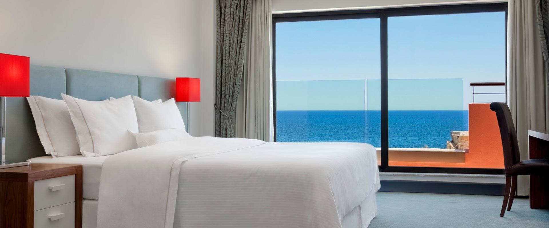 luxury resort suite bedroom with an ocean-view terrace