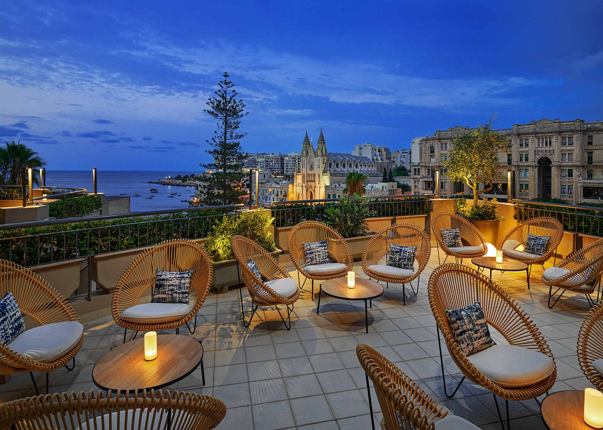 a luxury hotel restaurant terrace with candle-lit tables overlooking historic Malta and Mediterranean sea sea