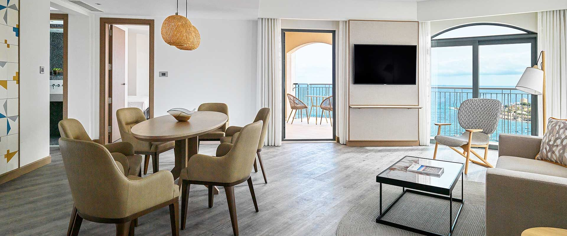 a spacious luxury hotel suite living area with modern furnishings and a terrace overlooking the mediterranean sea