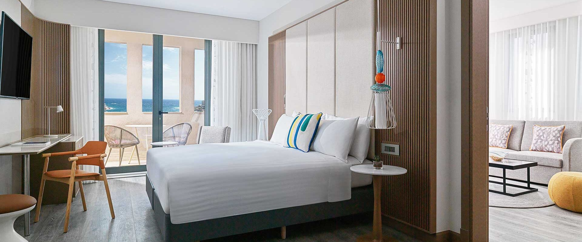 the spacious bedroom of a luxury hotel suite with bed doors leading to a balcony with sitting area overlooking the sea
