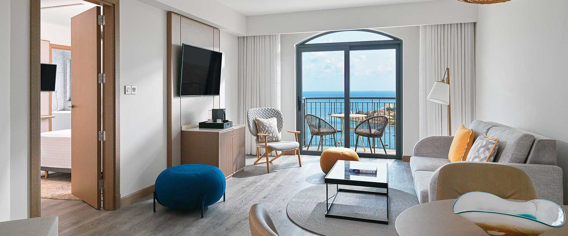a luxury hotel suite living area with dining room table and sitting area and a balcony overlooking the mediterranean sea